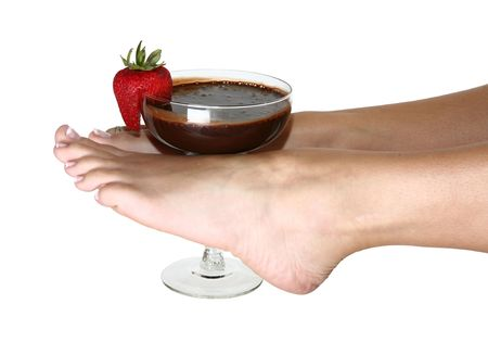 Womans feet holding glass of chocolate sauce and strawberry.  Clipping path included.