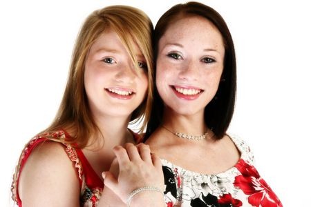 Beautiful 17 year old and 15 year old teen sisters over white. photo