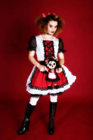 Beautiful young hispanic woman dressed as doll holding matching ragdoll.