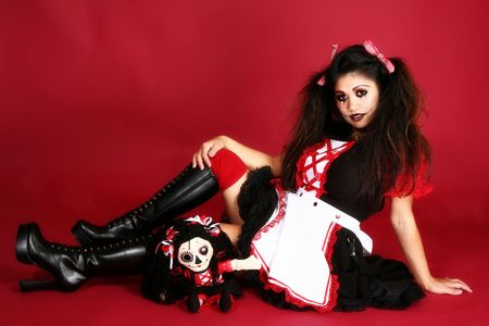 Beautiful Filipino woman dressed as doll over red background.