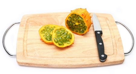 english cucumber: Kiwano or African horned melon sliced open over white. Also known as hedged gourd, African Horned Cucumber, English tomato.