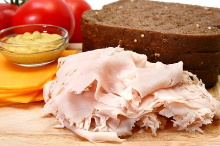 Makings of a turkey sandwich includeing dark german wheat, sliced turkey, tomatoe, spicey mustard, cheddar cheese. Imagens