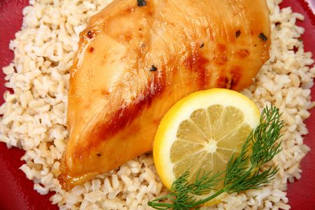 Lemonade Chicken and brown rice with lemon slice and dill.