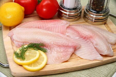 tilapia: Fresh Ttilapia with tomato, lemon, dill on cutting board.  St. Peters fish.