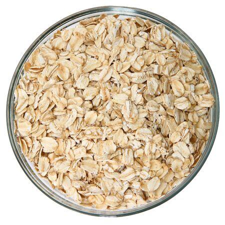 Glass bowl of raw oats over white background. Фото со стока