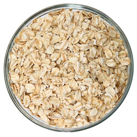 Glass bowl of raw oats over white background. Stock Photo