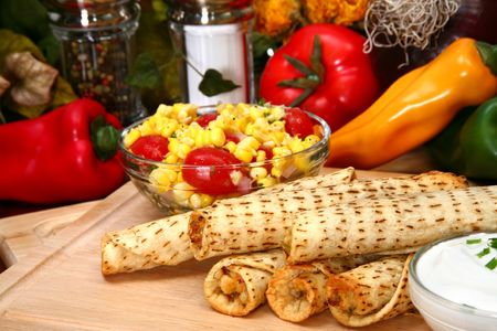 Stack of chicken taquitos with hot sauce and sour cream in kitchen or restaurant Imagens - 2951059