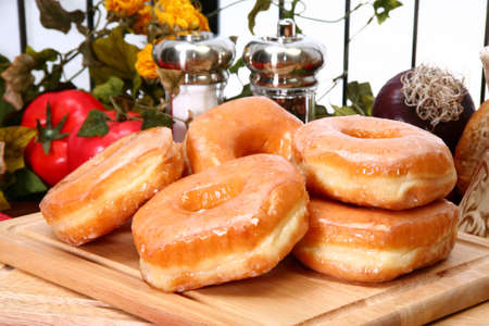 Stack of fresh baked glazed donuts in kitchen or restaurant. 스톡 콘텐츠