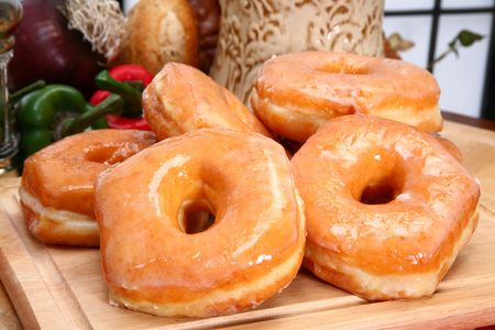Stack of fresh baked glazed donuts in kitchen or restaurant. Standard-Bild