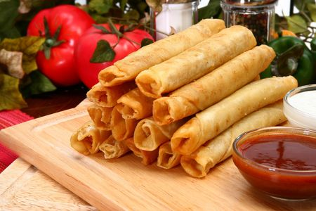 Stack of chicken taquitos with hot sauce and sour cream in kitchen or restaurant photo
