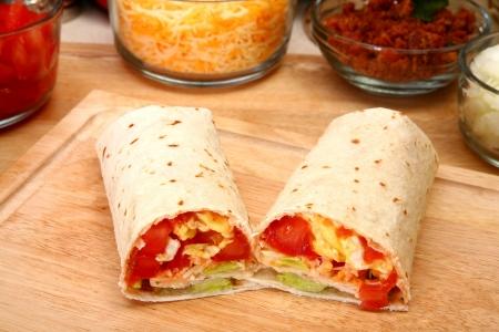 Breakfast burrito in kitchen or restaurant.  Eggs, cheese, tomato, lettuce, onion, chipotle, bacon.
