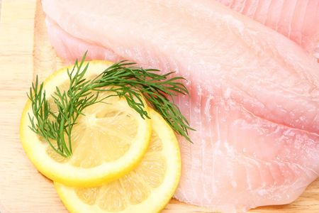 Fresh Ttilapia with tomato, lemon, dill on cutting board.  St. Peter's fish. Stock Photo - 3150934