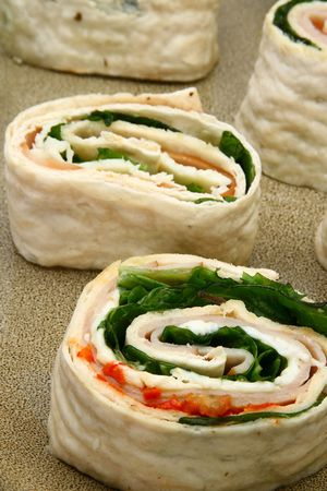 Spicy ham, provolone and spinach wrap with ranch dressing on side. Imagens