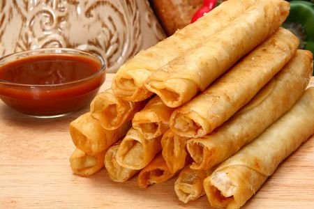 Stack of chicken taquitos with hot sauce and sour cream in kitchen or restaurant Standard-Bild