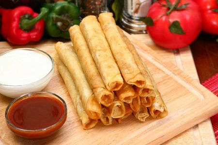 Stack of chicken taquitos with hot sauce and sour cream in kitchen or restaurant Imagens
