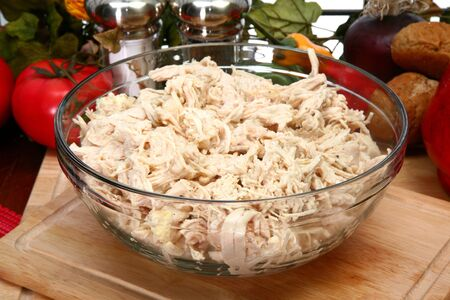 Bowl of shredded chicken breast in bowl in kitchen or restaurant.