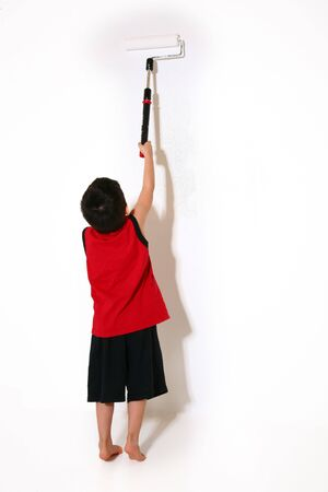 children painting: Five year old boy painting white wall.