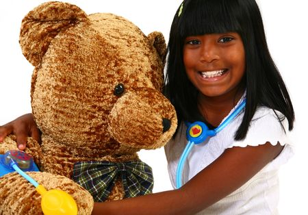 Beautiful 10 year old Indian girl playing doctor to a giant teddy bear. photo