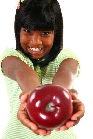 sharing food: Beautiful happy 10 year old Indian girl sharing apple. Stock Photo