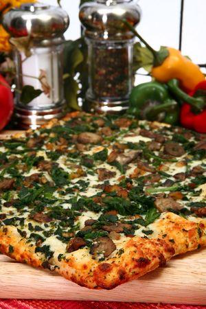Spinach mushroom pizza in kitchen.