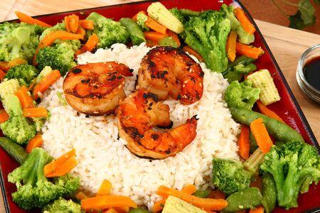 Ginger Teriyaki Shrimp with rice and veggies in kitchen or restaurant. photo
