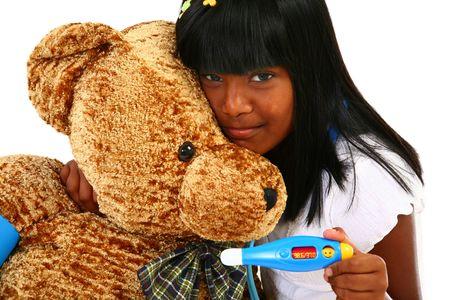 Beautiful Indian girl playing nurse to giant teddy bear. photo