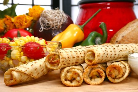 Stack of chicken taquitos with hot sauce and sour cream in kitchen or restaurant Stock Photo