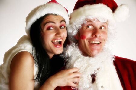 fake smile: Beautiful young middle eastern woman kissing fake santa.