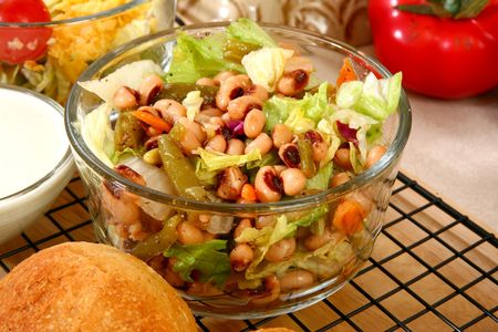 Glass bowl of black eye pea salad in kitchen or restaurant.