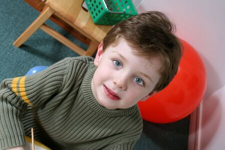 Handsome and happy little boy sitting in a pre-school.  Shot with the Canon 20D.