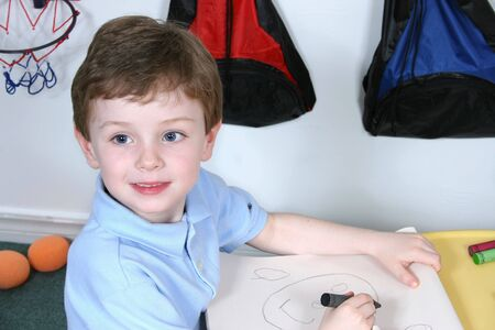 Handsome and happy little boy sitting at a pre-school table coloring with jumbo crayons.  Shot with the Canon 20D.