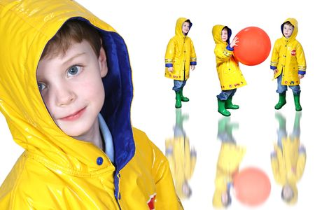 Four year old boy with big blue eyes in a yellow rain coat and green frog boots Stock Photo - 3686853