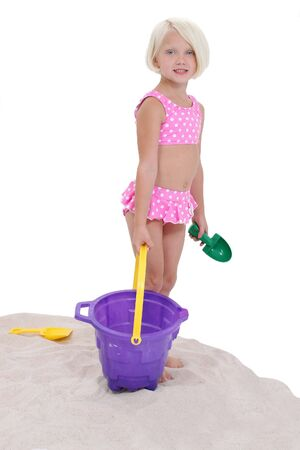 Beautiful Little Girl In Pink Swim Suit With Beach Toys.  Standing in Sand.  Shot in studio. 版權商用圖片