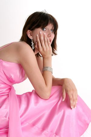 nosering: Beautiful sixteen year old girl in pink formal or prom dress. Dark hair and blue eyes. Shot in studio over white.