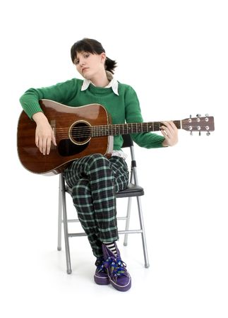 Young woman with acoustic guitar. Full body sittiing in chair. Shot in studio over white. photo