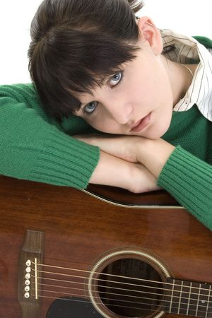Young woman with acoustic guitar. Green sweater, black hair, blue eyes. Shot in studio over white. photo