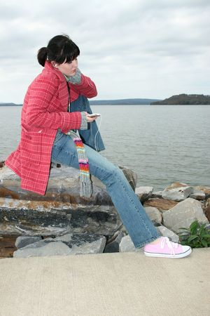 seventeen: Beautiful young woman sitting on rock by the lake listening to digital music on headphones.