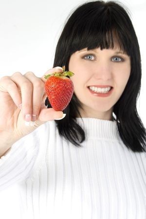 Beautiful young woman holding fresh strawberry. Shot in studio over white. photo