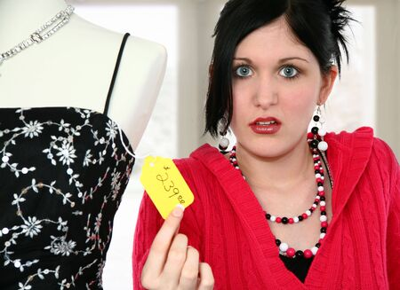 disgusted: Beautiful young woman disgusted with price tag on dress. Stock Photo