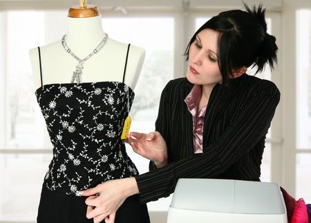 sales person: Beautiful retail sales person adjusting mannequin.
