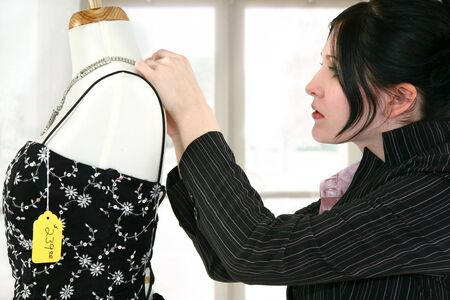 shoppe: Woman adjusting a necklace on a mannequin in a dress shoppe.