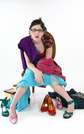 Woman in formal chair surrounded by shoes and dresses. Frustrated with shopping.