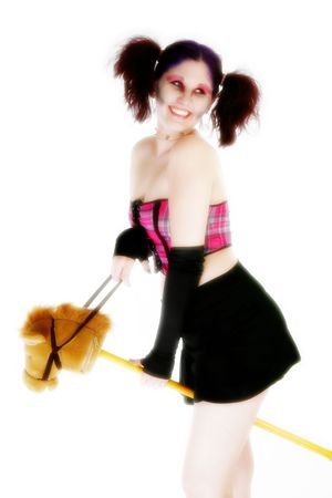 18 year old: High key potrait of beautiful 18 year old girl in goth make-up and purple tinted hair and toy horse.
