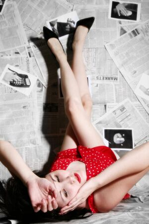 Beautiful young woman laying with feet up on newspaper background. photo
