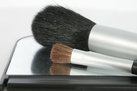 Two make-up brushes sitting on small mirror.