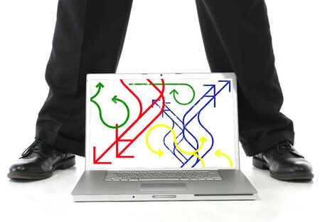 Mans feet on either side of laptop computer.  Screen showing red, blue, green and yellow arrows. photo