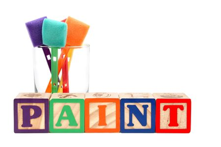 Glass of colorful paint sponges behind the word &quot,paint&quot, spelt with alphabet blocks photo