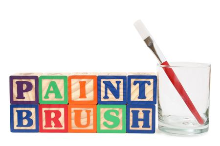 Glass with red paint brush beside the word &quot,paint brush&quot, spelt with alphabet blocks photo