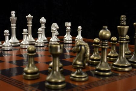 Wooden chess board with metal peices.  Shot in studio on black from corner to corner.  Focus on light pieces. Stock Photo - 3745748