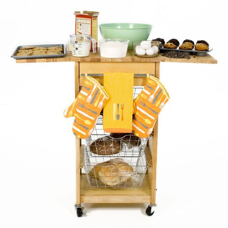 Kitchen cart filled with cake ingredients, cookies, muffins and fresh baked bread.